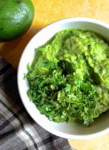 A white bowl with fresh homemade guacamole garnished with cilantro leaves. A checked grey and brown napkin to the left and part of an avocado seen on the top left corner