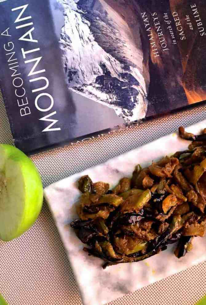 Fried eggplant with green apples cooked in spices, on a white marble slab, a slice of green apple on the left and a book on the Himalaya mountains above it