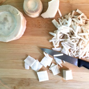 Rounds of bamboo shoots being sliced into thin juliennes for making curry