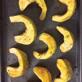 Peeled pumpkin sliced into crescents and drizzled with olive oil, pepper salt and rosemary, ready for baking