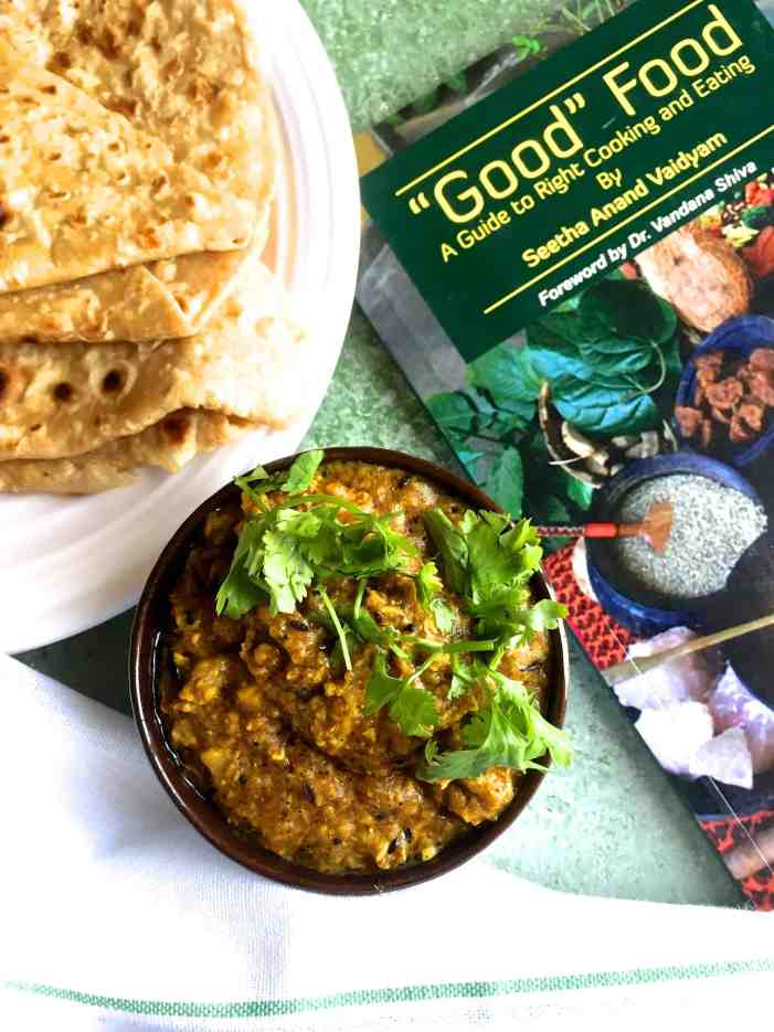 A bowl of corn curry with chapatis and with a book on Good Food alongside