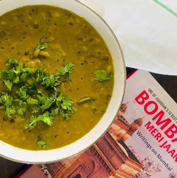 Comfort food Maharashtrian Amti Dal with Goda Masala in a large bowl with coriander leaves garnish and a book on Mumbai alongside