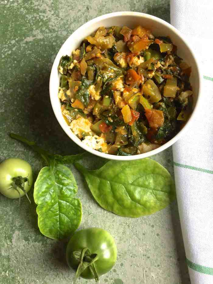 Radish Greens Spinach Curry in a white bowl with green tomatoes and Malabar spinach leaves on a green background and a white napkin striped with green on the side