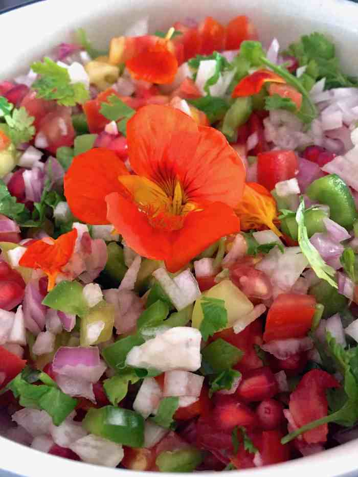 Sliced seasonal vegetables garnished with an orange edible flower with a citrusy dressing
