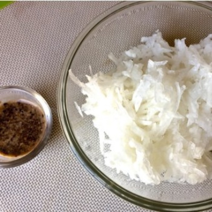 Grated white radish in a glass bowl with a smaller glass bowl of black sesame paste, all on a dull white background