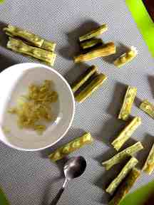 A white bowl with some scopped out moringa seeds. A few moringa drumstick pieces scattered on the grey background. Some sliced into two vertically, showing the seeds, some empty after the seeds have been scopped out with a spoon