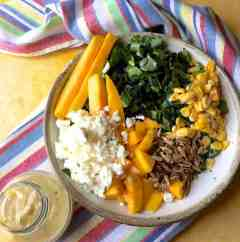 Seen from above: a white grey edged bowl with long slices of ripe yellow mango, shredded kale, grated cheese, roasted sunflower seeds and mango slices. A jar of tahini citrus salad dressing at the bottom left and a rainbow striped napkin curving below the bowl, all on a yellow background