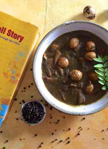 A white bowl with quail eggs in a pepper tamarind gravy. A yellow covered book with the name 'The Tamil Story' in Red, on the left and a bowl of pepper and scattered peppercorns in the foreground. A few speckled quail eggs in the background
