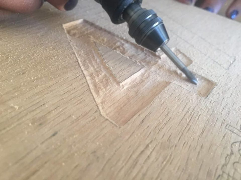 Closeup photo of the Dremel multi-tool being used to engrave the number four into a piece of basswood
