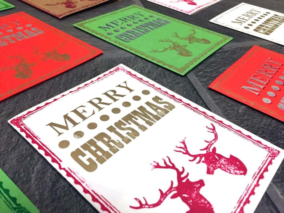 Closeup photograph showing handmade letterpressed christmas cards that read merry christmas