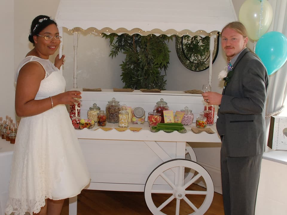 myself and my husband at our wedding reception. Here we are standing next to our candy cart which is full of sweets!