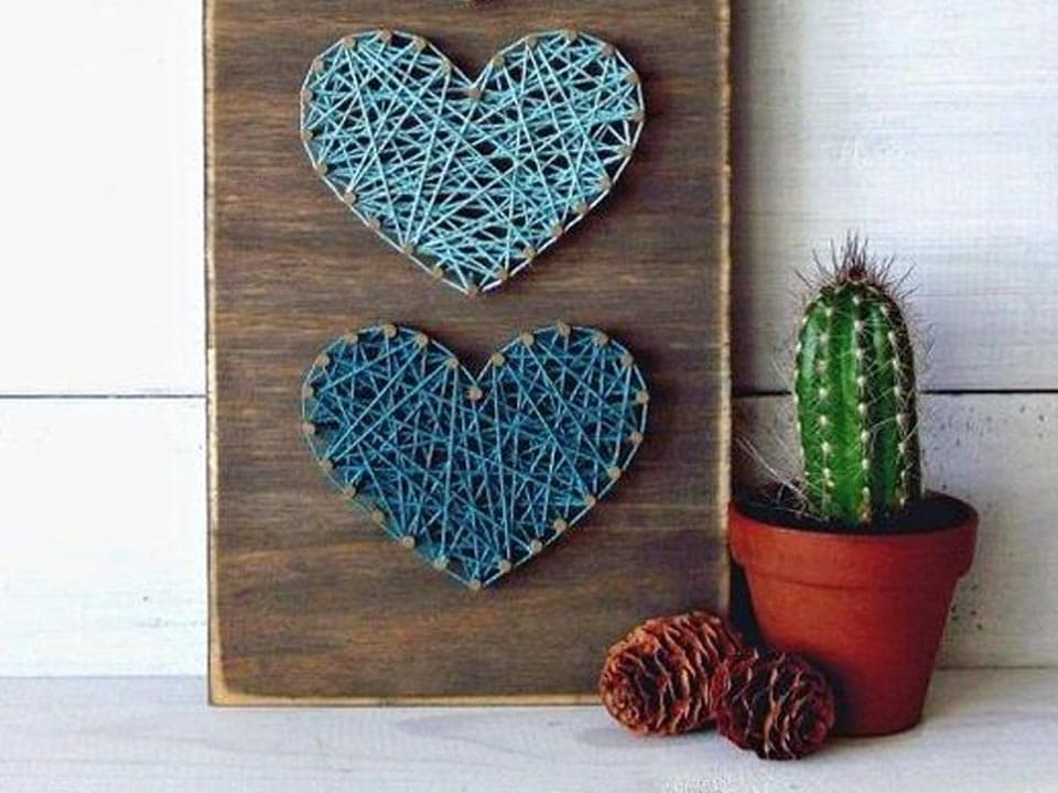 Blue string art hearts on rustic wood. Valentines day craft ideas