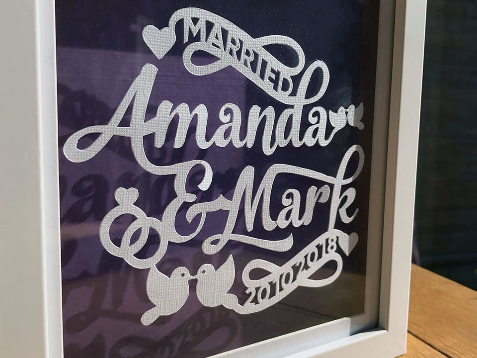 Typographic papercut design mounted inside a frame on a purple backgroun