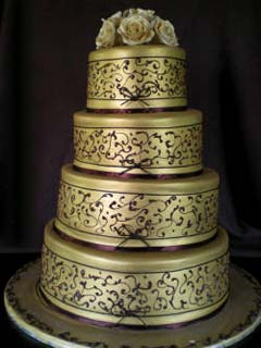 Two Tier Gold And White Wedding Cake With Ribbon Arranged As A Topper