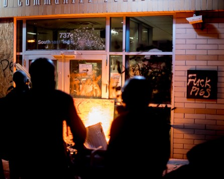 Protesters set a fire in a garbage can outside the police precinct building.