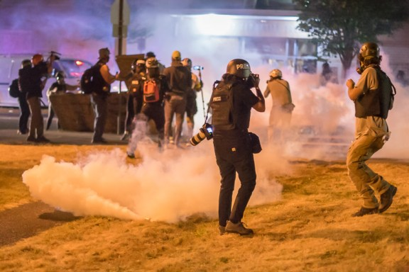 Police fire tear gas grenades at reporters.