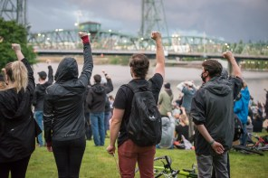Protesters raise their fists at a rally near the Hawthorne Bridge.