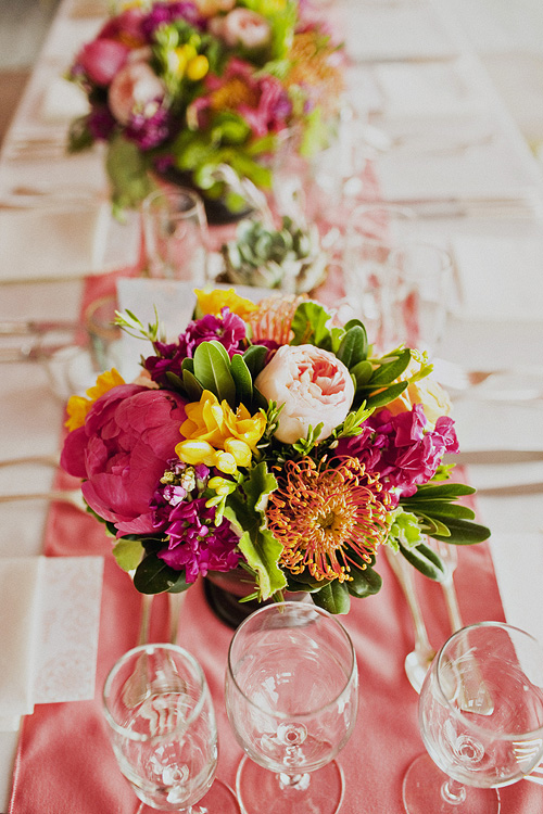 Bright centerpieces and coral runners create a romantic and lively vibe. Hana Floral Design, photo by Sloan Photographers.
