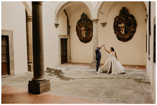 couple dancing in courtyard at italian wedding venue. bride is wearing eco friendly, timeless, wedding dress in ballgown style available in half sizes ensuring the perfect fit