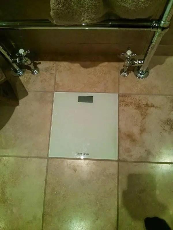 Balanza incrustada al detalle en un piso de baño.