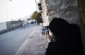 A Bahraini woman uses a mobile phone to take photos during clashes with riot police in the village of Sitra, south of the capital Manama, on January 8, 2016, following a protest against the execution of prominent Shiite Muslim cleric Nimr al-Nimr by Saudi authorities. Nimr was a driving force of the protests that broke out in 2011 in the kingdom's east, an oil-rich region where the Shiite minority of an estimated two million people complains of marginalisation. AFP PHOTO / MOHAMMED AL-SHAIKH   / AFP / MOHAMMED AL-SHAIKH        (Photo credit should read MOHAMMED AL-SHAIKH/AFP/Getty Images)