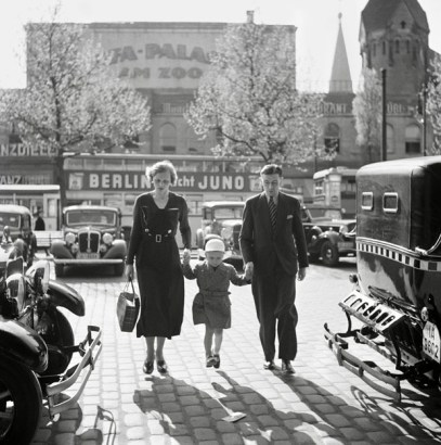 Una familia alemana camina entre taxis enfrente del cine Ufa-Palast de Berlín. Fines de los 1920 o principios de 1930. A German family walks between taxicabs in front of the Ufa-Palast movie theatre in Berlin, late 1920s or early 1930s.
