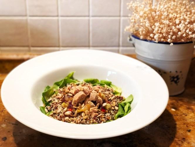 En la foto se muestra un plano de la ensalada de quinoa, verduras, atún y pipas acompañado de rúcula.