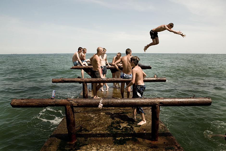 5. UKRAINA, Odessa. Chłopaki się popisują, a dzieczyny patrzą z zatłoczonej plaży. (Fot. Thomas Alboth)