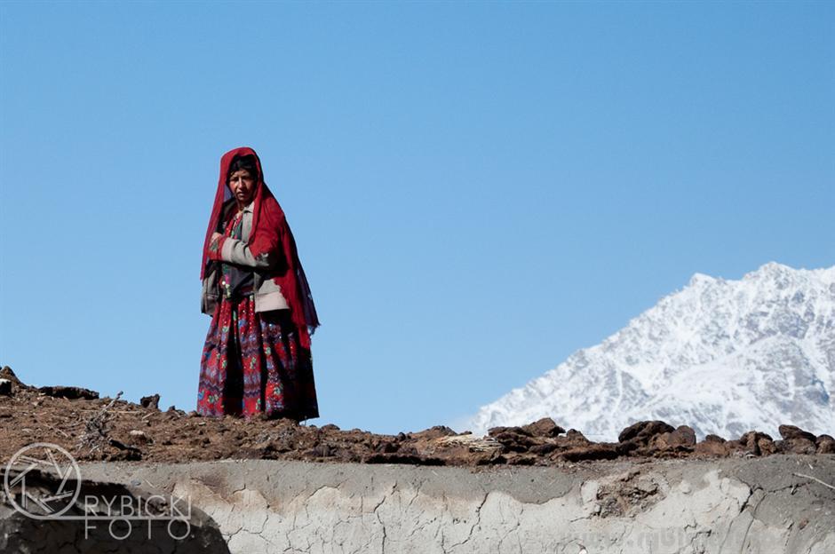 15. AFGANISTAN, prowincja Badachsztan. Kobieta na dachu domostwa dogląda suszących się plackoów z odchodów zwierząt – podstawowego opału w tym bezdrzewnym terenie. (Fot. Jakub Rybicki)