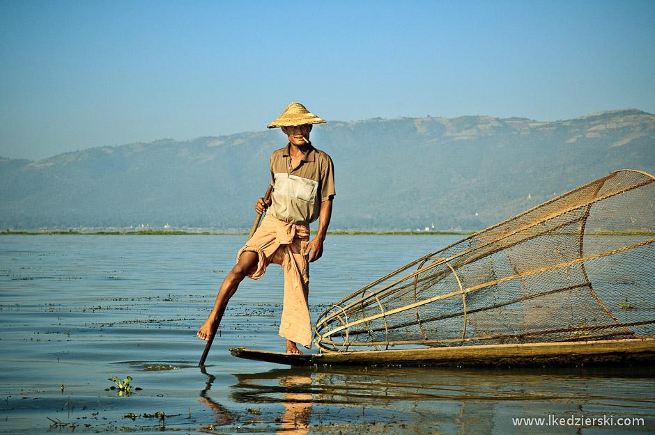 Birmańscy rybacy wiosłujący nogami na jeziorze Inle
