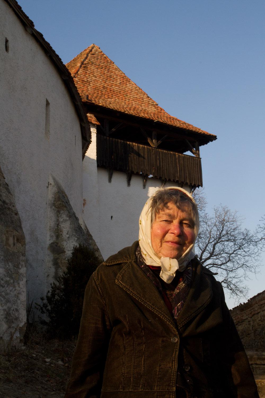 Una anciana guía frente a uno de los muros de la iglesia fortificada de Viscri