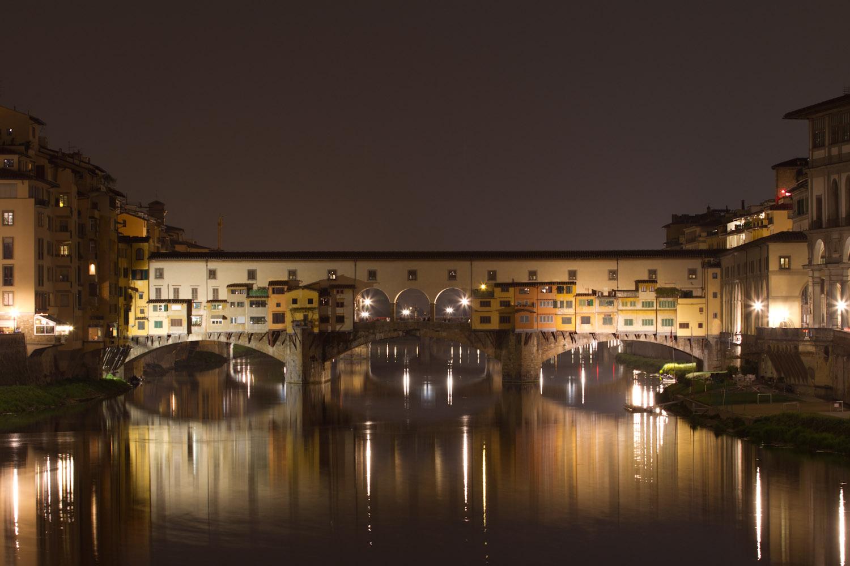 Vista nocturna del Ponte Vecchio con el río Arno corriendo a sus pies
