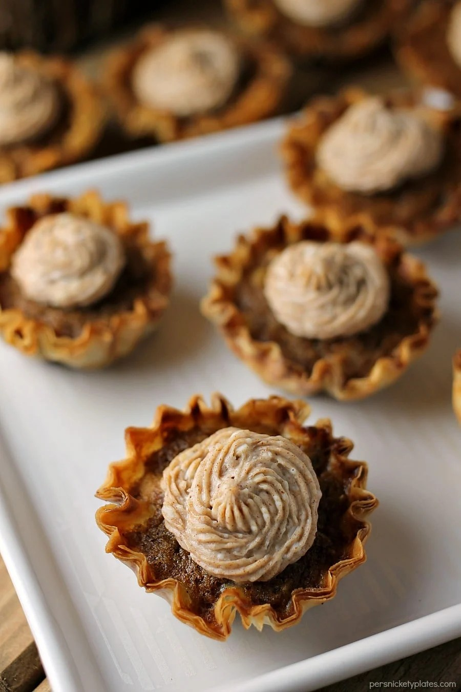 Mini Sweet Potato Pies with Cinnamon Cream Cheese Frosting are super easy to make but look fancy. Impress your guests with these bite sized treats! | www.persnicketyplates.com