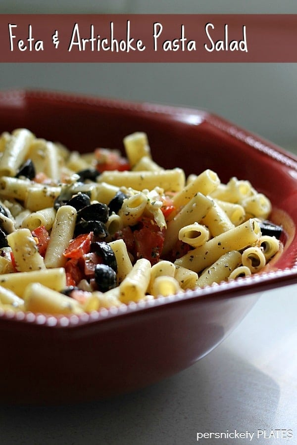 red bowl of pasta salad with feta & artichoke pasta salad text overlay