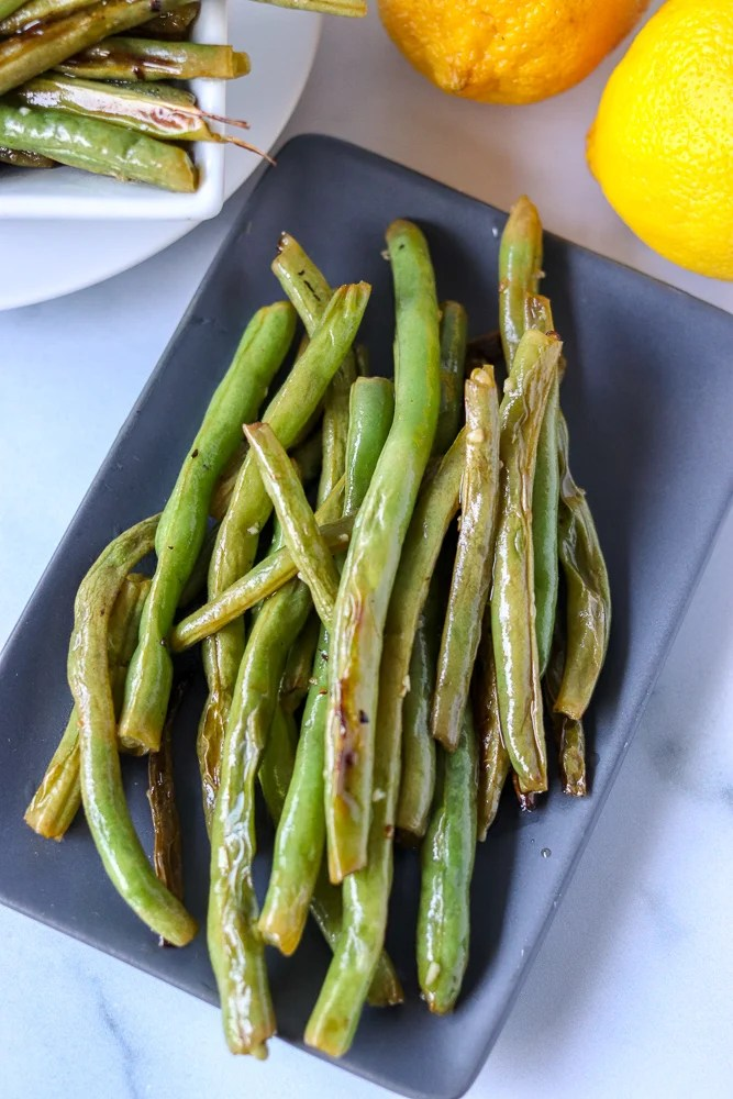 garlic green beans on grey platter with lemons in background