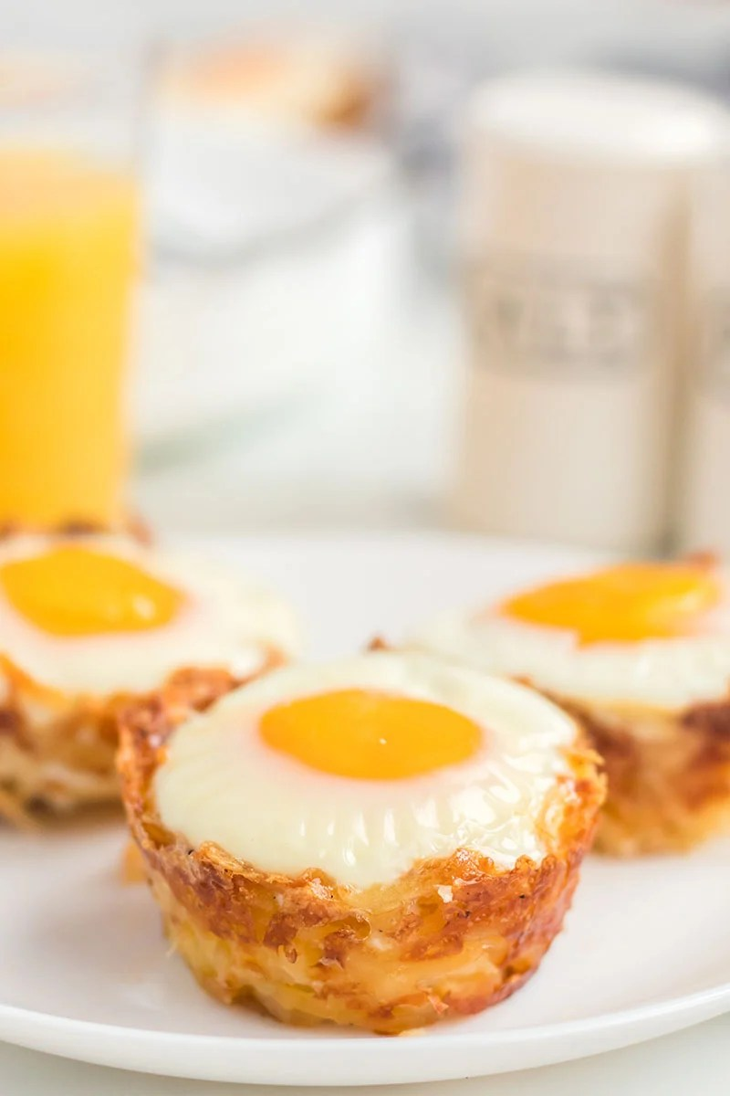 three hash brown egg cups on a white plate