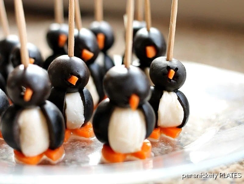 These Olive Penguins are made with black olives, mozzarella balls, and carrots. They are an adorable and fun appetizer, perfect for game day or small gatherings. These delicious poppers are almost too cute to eat!