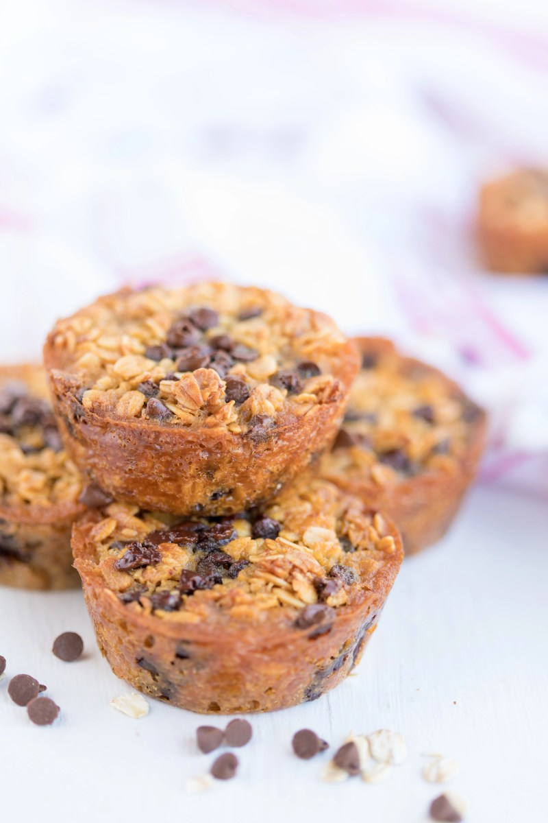 stack of 4 baked oatmeal chocolate chip breakfast cups with scattered chocolate chips