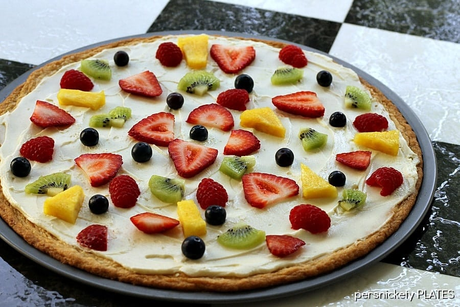 "Sugar Cookie Fruit Pizza -a thin sugar cookie ""crust"" spread with a cream cheese ""sauce"" and topped with strawberries, raspberries, kiwi, blueberries, pineapple - whatever fruit you love!"