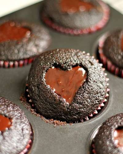 Dark chocolate cupcakes with a heart shaped cut-out filled with chocolate ganache and topped with sprinkles. Perfect for Valentine's Day!