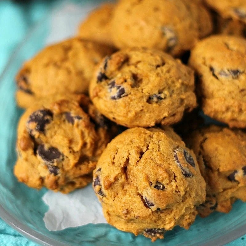 Close up of a platter of pumpkin chocolate chip cookies on a clear plate and a teal napkin