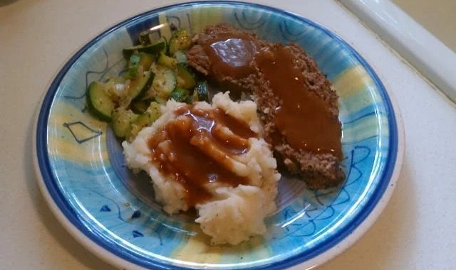 meatloaf, mashed potatoes & gravy, and zucchini on a plate