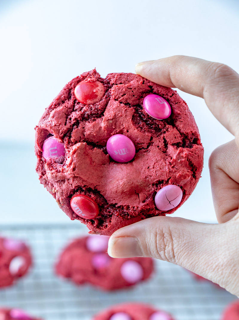 hand holding a red velvet cookie with M&Ms