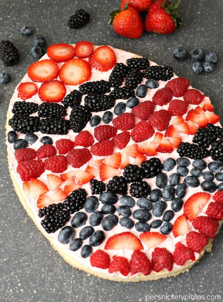 """A festive Easter egg sugar cookie fruit """"pizza"""" with strawberry cream cheese frosting. You can make it super simple with a sugar cookie mix or make it from scratch.   Persnickety Plates"""