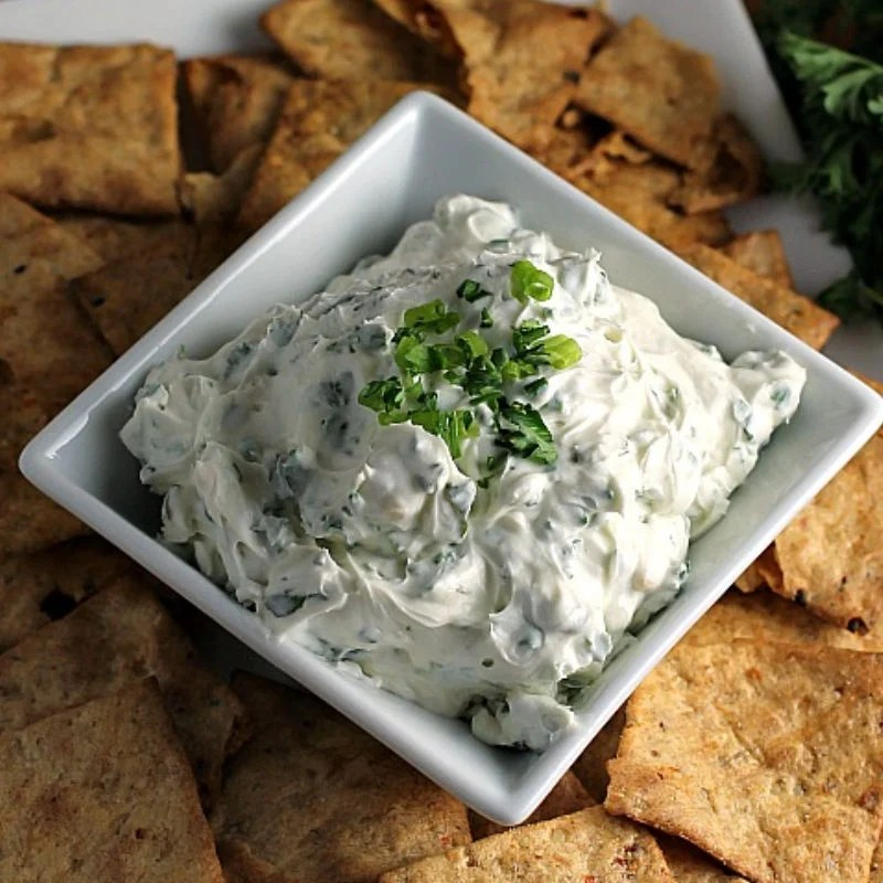 garlic herb dip in square bowl surrounded by chips