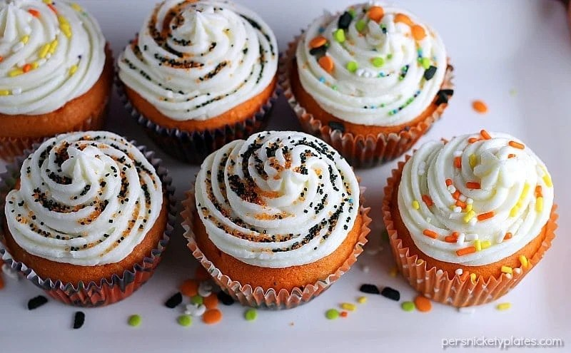 "Brownie Bottom Halloween Cupcakes have a layer of dark chocolate brownie topped with orange cake batter and finished off with buttercream and sprinkles. They are the perfect mix of semi-homemade and ""from scratch"" to be easy but really fun and festive for your next Halloween party! 