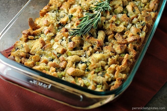 traditional herb stuffing in a casserole dish topped with rosemary