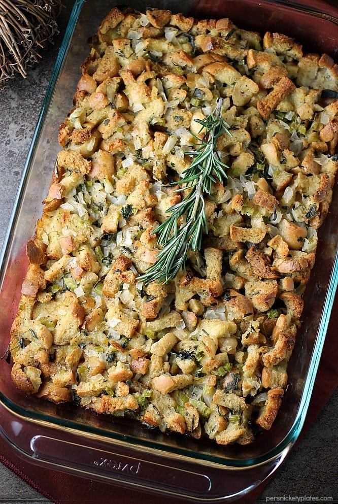 overhead shot of herb stuffing in a baking dish topped with rosemary