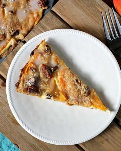 Peach Crumble Fruit Pizza is made on a cake batter crust, piled with thinly sliced fresh peaches and topped with a crumble and pecans and drizzled with a cinnamon sugar glaze. | www.persnicketyplates.com