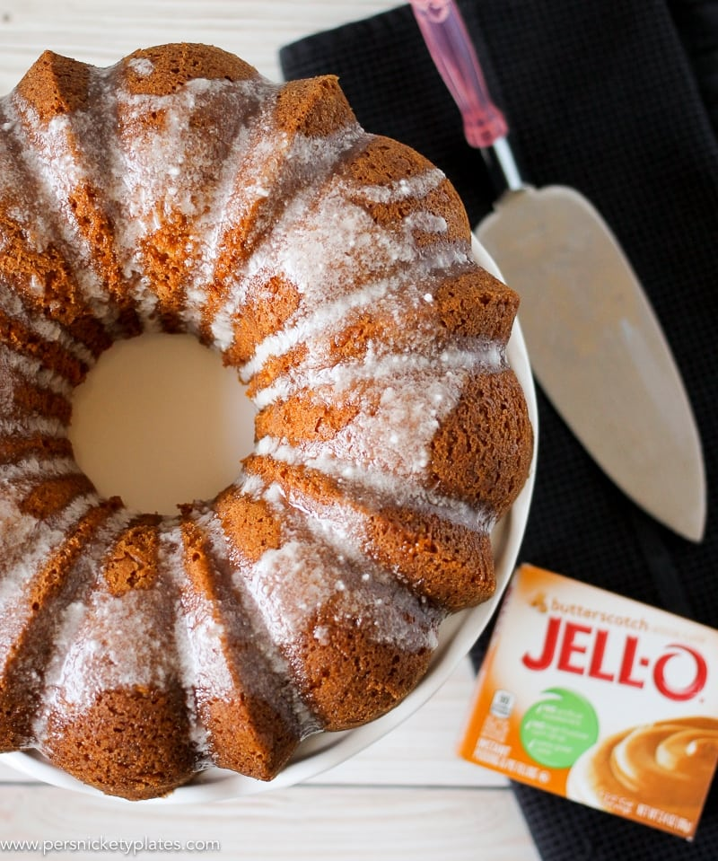 overhead shot of butterscotch bundt cake with a serving knife and jello